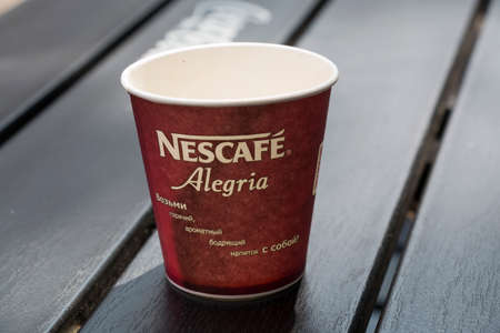 advertizing: PYATIGORSK, RUSSIA - AUGUST 11, 2014: Empty disposable glass of Nescafe with an advertizing slogan in Russian: Take hot, fragrant invigorating drink with itself!