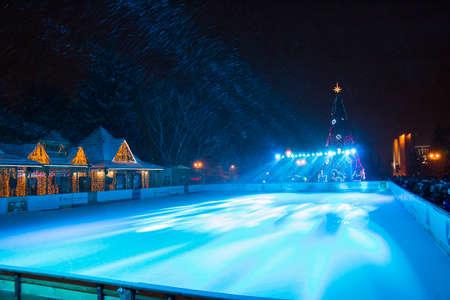 PYATIGORSK, Rusia - 31 de diciembre 2014: Vista de la pista de patinaje sobre hielo al aire libre y el árbol de Navidad en frente de la administración de la ciudad de Pyatigorsk