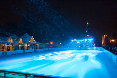 skating rink: PYATIGORSK, RUSSIA - DECEMBER 31, 2014: View of the outdoor ice skating rink and Christmas tree in front of the administration of the city of Pyatigorsk