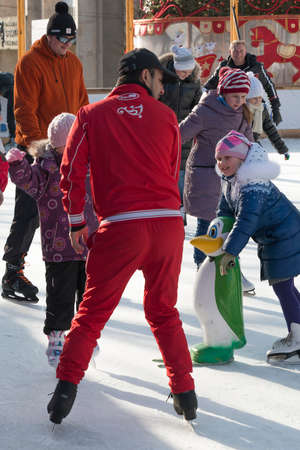 PYATIGORSK, RUSSIA - JANUARY 4, 2015: Open-air ice rink. Trainer teaches kids to skate