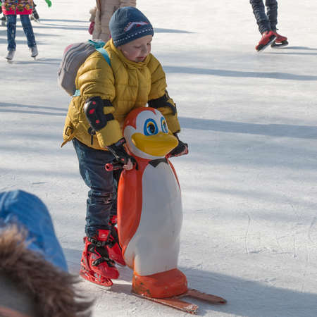 PYATIGORSK, RUSSIA - JANUARY 4, 2015: Open-air ice rink. A boy learns to ride holding support for beginners in the form of a penguin