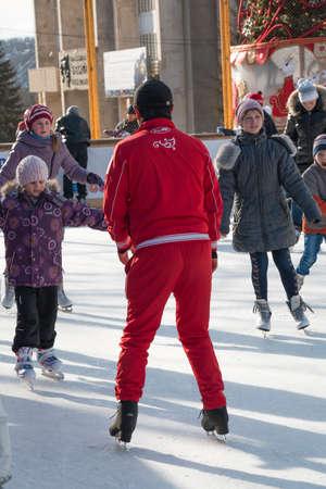 pyatigorsk: PYATIGORSK, RUSSIA - 4 gennaio 2015: pista di pattinaggio all'aperto. Trainer insegna ai bambini a pattinare