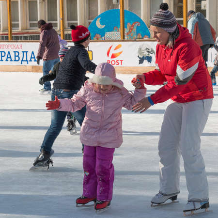 duffle: PYATIGORSK, RUSSIA - JANUARY 4, 2015: Open-air ice rink. Mother teaches daughter to stand on skates Editorial