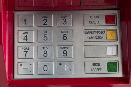 bankomat: Metallic pinpad ATM or payment terminal on a red background