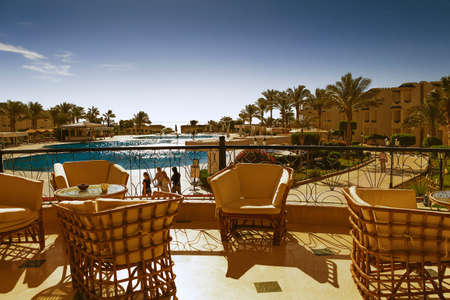 cane chair: SHARM EL-SHEIKH, EGYPT - NOVEMBER 30, 2014: tables and chairs on the terrace of the hotel Grand Oasis Resort in hot weather
