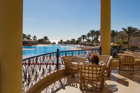 admires: SHARM EL-SHEIKH, EGYPT - NOVEMBER 30, 2014: Woman admires the view from the terrace to the hotel Grand Oasis Resort
