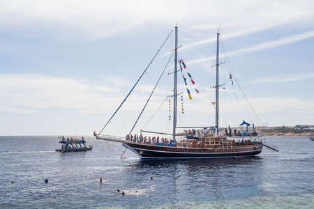 Sharm el-Sheikh, Egypt - December 2, 2014: Sailing yacht with tourists on board off the coast of the Red Sea