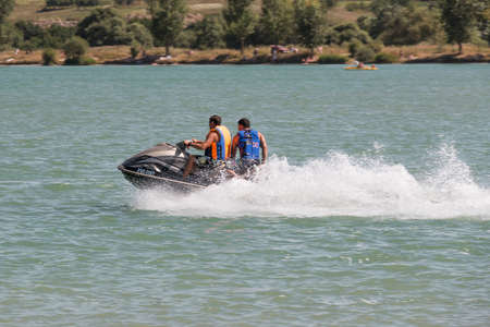 pyatigorsk: Pyatigorsk, Russia - August 3, 2014: Two men on a water scooter ride fast on the lake Editorial