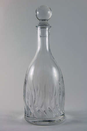 decanter: Crystal decanter with highlights on a gray background, side view Stock Photo