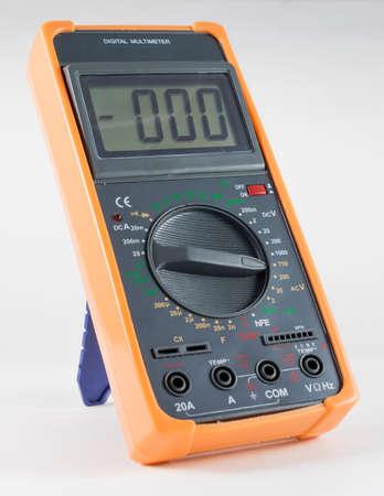 Black Digital Multimeter with orange bumper on white photo