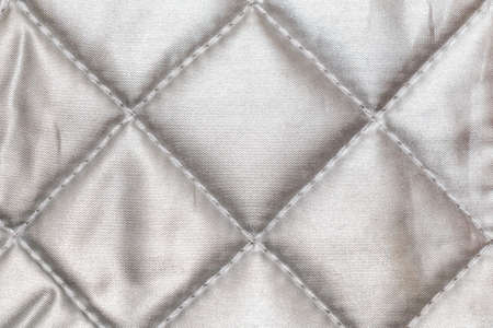 wadded: The texture of shiny fabric stitched squares, background