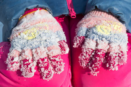Lumps of frozen snow on woolen gloves in the winter Stok Fotoğraf