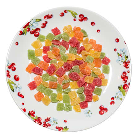 candied fruits: Multi-colored candied fruits on porcelain plate with an ornament in the form of berries, top view