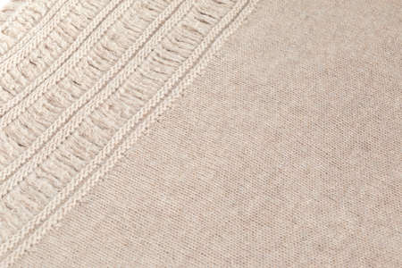 textile  texture: Cream woolen fabric with a pattern at an angle to the viewer, background