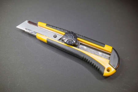 retractable: Utility knife with a retractable blade and yellow plastic handle with rubber insert