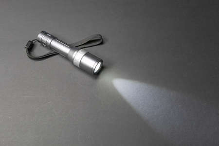 wrist strap: Glowing metal flashlight with wrist strap on a dark background Stock Photo