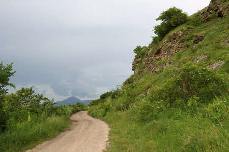 mountainous: Dirt road in a mountainous area in cloudy weather