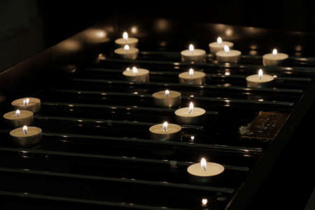 priesthood: Background of many lit candles on a dark background in basilica
