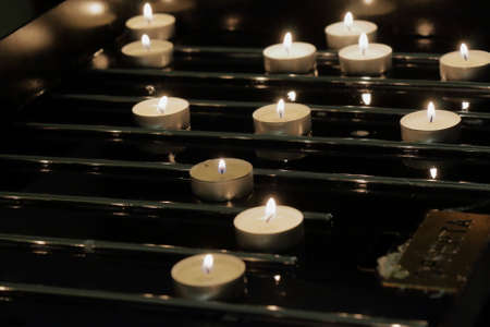 lit collection: Candles burning in a church on a dark background