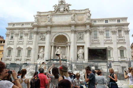 take a history: Rome, Italy - August 16, 2015: Tourists take pictures of the Trevi Fountain and Palazzo Poli.