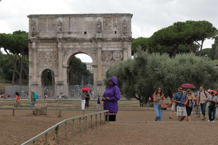 constantino: Rome, Italy - August 16, 2015: Tourists run away from a rain. Arch of Constantine Arco di Constantino in rainy weather Editorial
