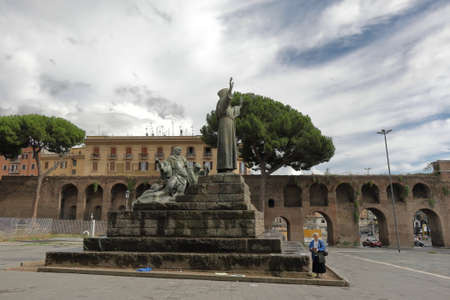passerby: Rome, Italy - August 16, 2015: Passerby and Statue of St Francis of Assisi Monumento a San Francesco di Assisi bronze sculptural group is work of Giuseppe Tonnini Editorial