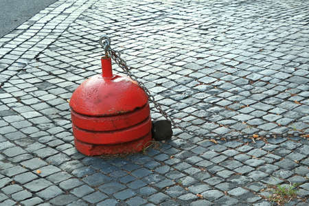 roadway: Red bollard with chain on black brick roadway at morning