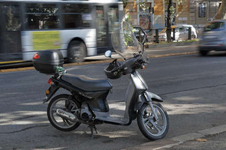handlebars: Rome, Italy - August 17, 2015: Black scooter with a top box and a helmet on the handlebars. Editorial