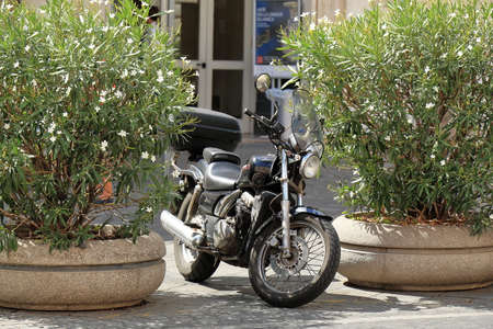 flowerbeds: Rome, Italy - August 17, 2015: Black classic motorcycle parked between two flowerbeds