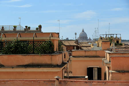 focus on a foreground: Rome, Italy - August 17, 2015: View on roof of buildings and dome of St. Peters Basilica italian: Basilica di San Pietro from Piazza del Quirinale. Focus foreground