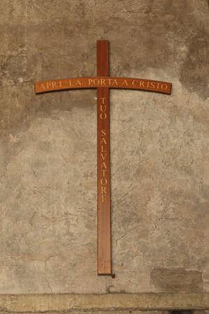 apri: Cross on a old stucco wall with inscription on italian: Apri La Porta a Cristo Tuo Salvatore Open the Door to Christ Your Savior