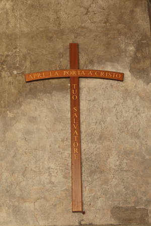 cristo: Cross on a old stucco wall with inscription on italian: Apri La Porta a Cristo Tuo Salvatore Open the Door to Christ Your Savior