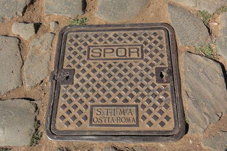 spqr: Rusty hatch in dust with inscription SPQR STIMA OSTIA-ROMA on the street of Rome