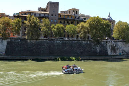 onboard: Rome, Italy - August 18, 2015: Boat with tourists sailing on the river Tiber in a bright sunny day