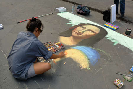 mona lisa: Florence, Italy - August 19, 2015: The artist paints a picture face of a Mona Lisa of colored chalk on the sidewalk Stock Photo