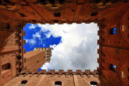 siena italy: Siena, Italy - August 20, 2015: Bottom-up view from courtyard of Torre del Mangia and Palazzo Pubblico in Siena, Italy.