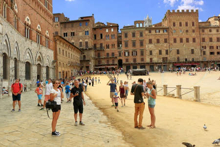 Siena, Italy - August 20, 2015: Tourists and buildings in Piazza del Campo in Siena, Italy Editöryel