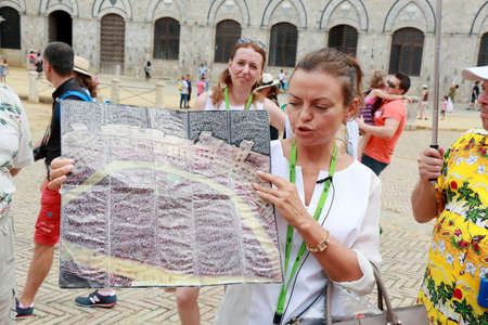 each year: Siena, Italy - August 20, 2015: The guide Irina tells tourists about the Palio di Siena horse race that is held twice each year
