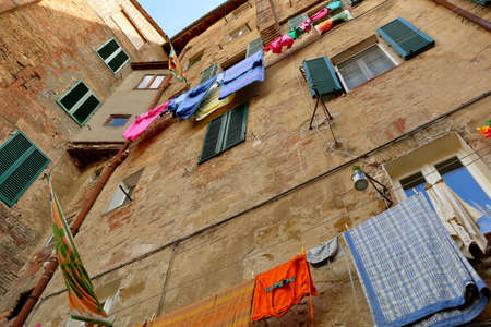 checker flag: Siena, Italy - August 20, 2015: Walls of the ancient building with windows and the drying linen