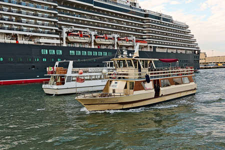 ms: Venice, Italy - August 21, 2015: Sailing yellow boat Motonavi Barracuda Venezia with red flag against the boat Bellini and Cruise Ship MS Queen Victoria