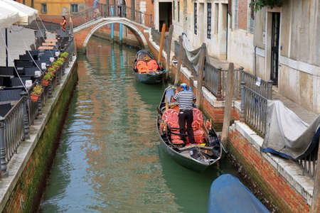 gondolier: Venice, Italy - August 21, 2015: Gondola with gondolier in Venetian canal near street cafe and bridge