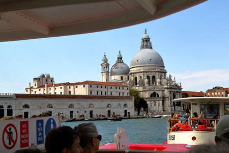 tourists stop: Venice, Italy - August 21, 2015: Tourists in vaporetto at water bus stop S. Marco. View towards Basilica di Santa Maria della Salute