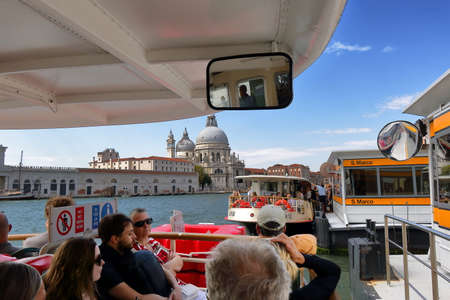 tourists stop: Venice, Italy - August 21, 2015: Tourists in vaporetto at water bus stop S. Marco near Basilica di Santa Maria della Salute