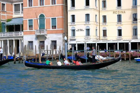 regina: Venice, Italy - August 21, 2015: Sailing in the gondola people by Grand Canal past the Westin Europa Regina hotel