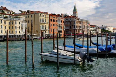 city park boat house: Venice, Italy - August 21, 2015: The parked motor boat and gondolas near wooden posts in Grand Canal