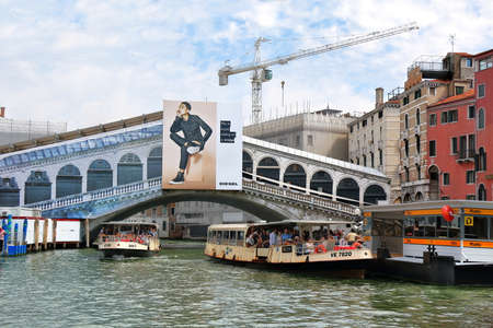 waterbus: Venice, Italy - August 21, 2015: View to the Rialto Bridge, waterbus stop and vaporetto in Grand Canal Editorial