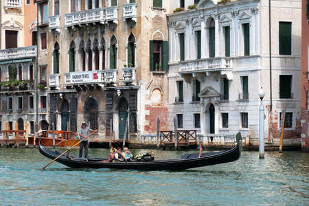 oar: Venice, Italy - August 21, 2015: Gondolier rowing oar in a gondola with passengers. Grand Canal in Venice. Editorial