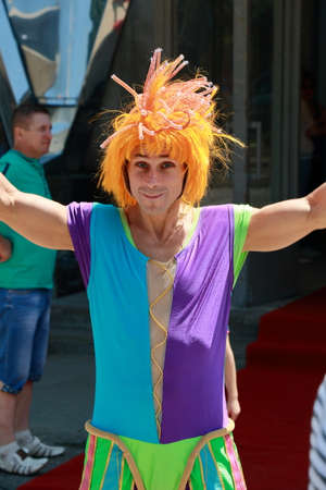 circus performers: Kislovodsk, Russia - July 18, 2015: Clown with orange wig near entrance to the circus. Kornilovs show Carnaval of Elephants Editorial