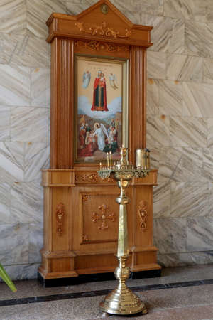 iconostasis: Burning candles in golden candlestick near the Icon in wooden frame. Narzan Gallery in Kislovodsk, Russia.