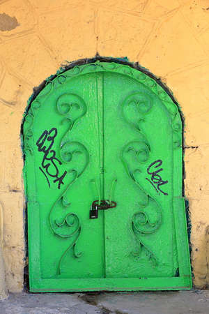 lock: Pyatigorsk, Russia - October 4, 2015: Old arched doors from metal painted in green with lock